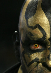 A New Orleans Saints fan sports a painted face and colored contact lens in the stands during game against the Miami Dolphins in a NFL football game in Miami