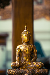 little statue in a temple with gold leave on it