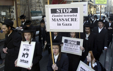 Members of Neturei Karta hold signs during protest in Jerusalem