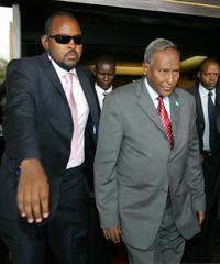 Somali President Abdullahi Yusuf is escorted out of closed-door meeting in Nairobi