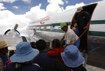 A Douglas DC-3S, or Super DC-3, is visited by local residents in Uyuni