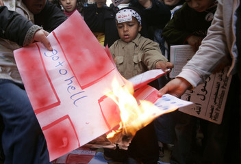 A Palestinian boy burns flag of Denmark during protest against Danish newspapers reprinting cartoons of Prophet Mohammad in southern Gaza Strip