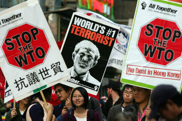 Anti-World Trade Organisation activists hold placards during protest march in Hong Kong
