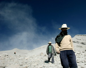 Residents walk at a side of the volcano Ubinas in the town of Ubinas, in the Moquegua region, some 5..