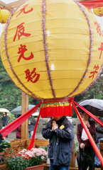 A WORSHIPER STANDS UNDER A HUGE LATERN AS HE PRAYS AT THE LONGSHAN TEMPLE IN TAIWAN.