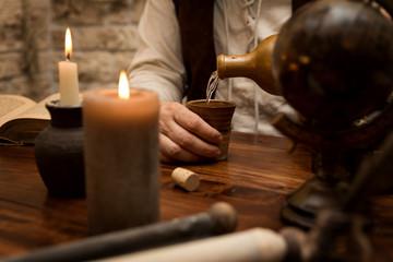 Ambiente Mittelalter, Mann schenkt sich trinken in den Becher