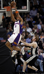 Phoenix Suns Shawn Marion dunks while being guarded by San Antonio Spurs Matt Bonner during first quarter NBA basketball action in Phoenix