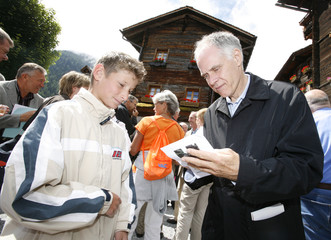 Swiss minister Leuenberger signs an autograph to a teenager during a meeting with the population of Grimentz during the second day of the annual field trip of the Swiss government