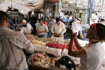 People buy sweets for the Eid al-Fitr in the downtown market area in Amman