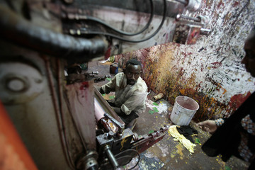 A worker fixes a machine as he talks to a plastics engineer at a plastic factory in Khartoum