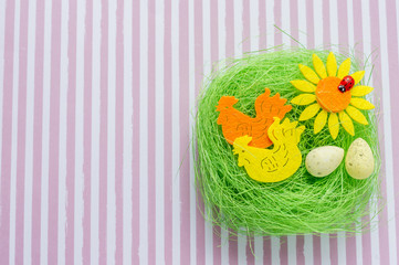 Green artificial nest with two colored cocks, egg and sunflower on striped background