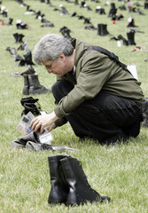 """Tony Heriza looks at boots which are part of """"Eyes Wide Open: An Exhibition on the Human Cost of the Iraq War""""  in Chicago"""