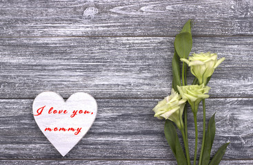 Decorative white wooden heart on grey wooden background with lettering Happy Mother's Day.