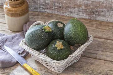 Round zucchini in a basket on a wooden table