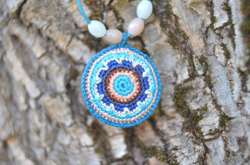 Handmade accessories in ethnic style on tree bark. Crochet homemade things. Crochet pattern. Handicraft manufacturing