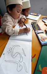An Indonesian Muslim boy practises coloring Arabic letters during a class in Sukabumi