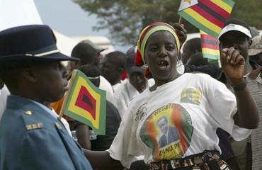 Supporters of Zimbabwe's President Robert Mugabe's ZANU-PF party cheer at an election rally at Mubaira