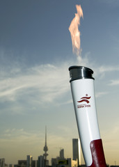 lit torch on road to Doha Asian Games is seen with Kuwait City background as the flame is carried through Kuwait