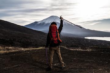 Tuinposter Alpinisme 登山をする男性、ステッキ、喜ぶ、歓喜 手を上げる