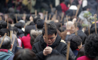 Worshippers holding incense pray at the Lungshan Temple on the first day of the Chinese Lunar New Year in Taipei