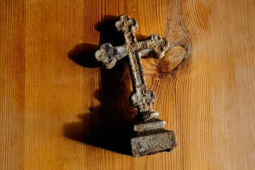 old iron cross on wooden table