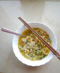Bowl of rice noodle soup with a pair of chopsticks.