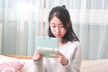 携帯ゲームをする女の子 小学生の女の子のポートレート
