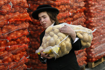 An Ultra-Orthodox Jewish youth carries a sack of potatoes for distribution to the needy in the Mea Shearim neighbourhood of Jerusalem