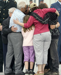 Family members of Corporal Martin Dube embrace on the tarmac at the Canadian Forces Base (CFB) Trenton