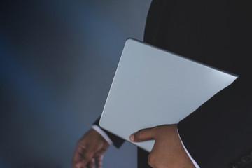 Part of Businessman in Black suit bring digital tablet, New gadget for modern business work concept, Dark tone, Selective focus on hand