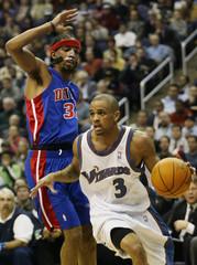 Wizards Juan Dixon tries to drive around Pistons Richard Hamilton.