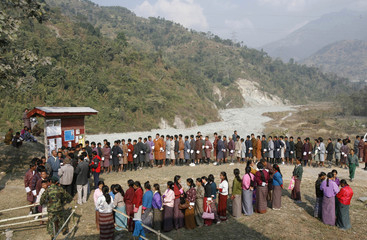 People stand outside a polling station in Pashakha village during Bhutan's first national council voting