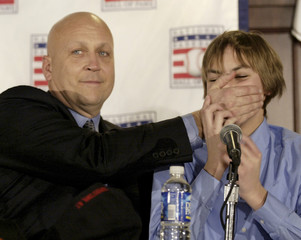 Ripken playfully puts his hands over his son Ryan's mouth during news conference in Baltimore