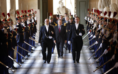 French national Assembly's speaker Accoyer walks between Republican Guards at the Chateau de Versailles, near Paris