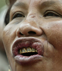 A Bolivian woman with heart shaped gold crowns on her teeth yells slogans during rally in La Paz.