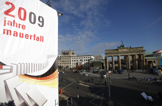 A logo advertising the 20th anniversary of the fall of the Berlin Wall  is seen near Brandenburg Gate as workers prepare the venue