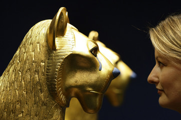 A woman poses next to a model of Pharaoh Tutankhamen's ritual bed during press preview of an exhibition in Munich