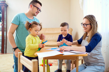 The family draws pencils at a table in room.
