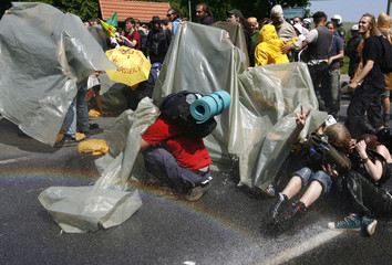 Anti-G8 protesters are sprayed with water from a water cannon as they stage a sit-in on a street in Hinter Bollhagen