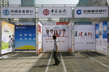 A man walks past booths belonging to major Chinese banks in Shenzhen