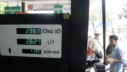 A worker pumps petrol into a motorcycle at a station in Hanoi