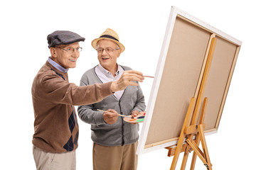 Two happy mature men painting on a canvas