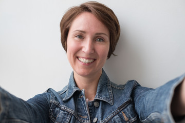 Portrait of a middle-aged woman in a denim jacket. She hugs someone or makes a selfie.