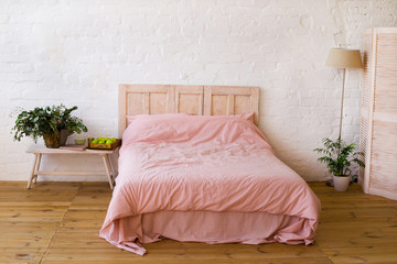 Empty bed with pink pillows and pink cover in the bedroom.