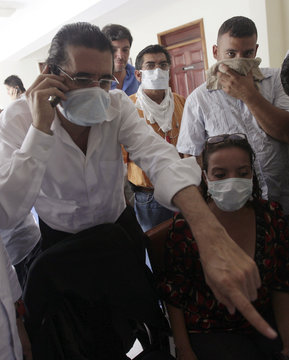 Honduras' ousted President Manuel Zelaya and his wife Xiomara Castro look at a computer while wearing surgical masks in the Brazilian embassy in Tegucigalpa