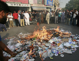 Shopkeepers burn compact discs and posters of movies after getting a warning from hard-line religious people to stop selling un-Islamic CD's in Lahore