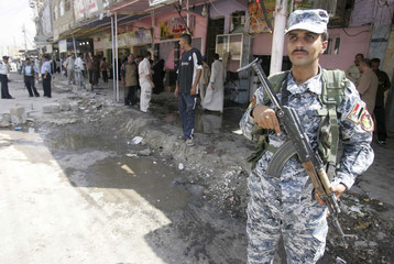 An Iraqi policeman stands guard at the site of a bomb attack in Babel Province