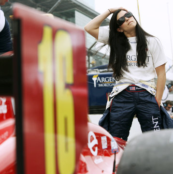 Driver Patrick of US stretches her neck muscles while standing near her car before practice at Indianapolis Motor Speedway