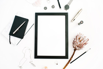 Blogger or freelancer workspace with blank screen photo frame, protea flower, notebook, watches and feminine accessories on white background. Flat lay, top view minimalistic decorated home office desk