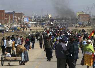Bolivian indigenous people walk on the main highway, which is blocked against cars, in El Alto